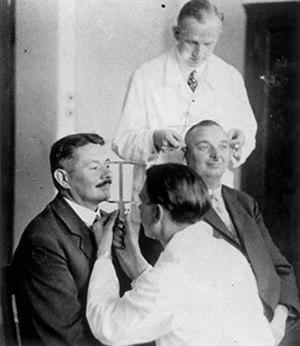 Otmar Freiherr von Verschuer - Otmar von Verschuer (rear) supervises the measurement of two men's head circumference as part of an anthropometric study of heredity.