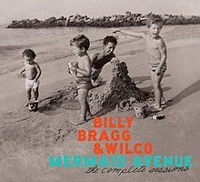 "A black-and-white photo of a man building a sand castle on a beach with several children standing around him, one of whom is pointing toward the body of water. Superimposed text reads ""BILLY / BRAGG / & WILCO"" in orange, ""MERMAID AVENUE"" in blue, and ""the complete sessions"" in black script."