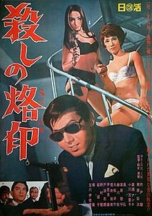 A man with prominent cheeks in sunglasses and a suit aims a gun. Two women stand on a spiral staircase behind him in their underwear also holding guns. Three men appear in an insert in the lower left corner.