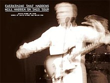 "A blurry black-and-white photo of a middle-aged Caucasian man in white overalls swinging his arms with a guitar slung over his shoulder. He is standing behind a microphone stand and in front of a man with a drum kit. In the upper left corner is written ""EVERYTHING THAT HAPPENS / WILL HAPPEN ON THIS TOUR /DAVID BYRNE ON TOUR / SONGS OF DAVID BYRNE AND BRIAN ENO"" in a stylized white font."