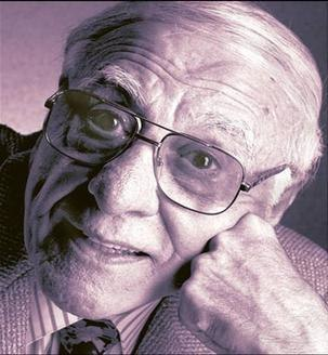 An old man wearing glasses, resting his cheek against his fist. The image is cropped just below the neck, though a striped dress shirt and tie are visible, covered by a blazer or suit coat.