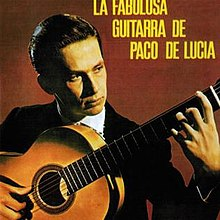 Man in black suit holding flamenco guitar in front of a reddish brown background