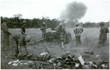 Soldiers operating a field gun. A large cloud of smoke is coming from the barrel while there is a pile of used shells to the rear