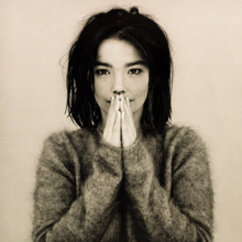 A picture of the album cover depicting a muted background with Björk standing facing forward in the middle. Björk is dressed in a fuzzy ragged sweater with her hands close together covering most of her mouth.