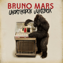 "A man wearing a gorilla costume standing next to a jukebox and holding it. The words ""Bruno Mars"" in red capital font are above the words ""Unorthodox Jukebox"" with capital font, both are on the top of the image."