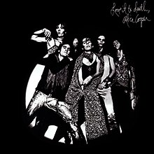 Black-and-white album cover. A group of five men in makeup pose together. The figure in the middle wears a cape and sticks his thumb out from behind it near his crotch.