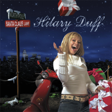 "A girl with blonde hair wearing a white sweater and blue jeans, throwing a red box into the air. She stands in front of a red electric scooter with several green and boxes on it, and a brown pole with two signs on top of it: a green one that reads ""NORTH POLE"" in capital letters on top, and a red one that reads ""Santa Claus Lane"" in capital letters below the other. Far behind her are a dark, starry sky and many buildings. Above the girl, ""Hilary Duff"" is written in cursive, white text."