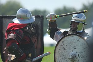 SCA armoured combat - Fighters practicing at Pennsic XXXVIII (2009). Note the use of rattan swords, edge padding on the shields, and bar grills added to the helmets