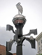 Photograph of the top of a lamp post-like apparatus. A bird figure sits atop a globe on the top, and four appendages jut out at ninety-degree angles from each other on the post.