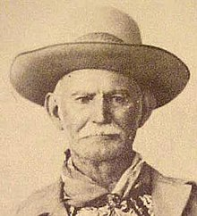 old man with moustache, wide-brimmed hat and bandana around neck