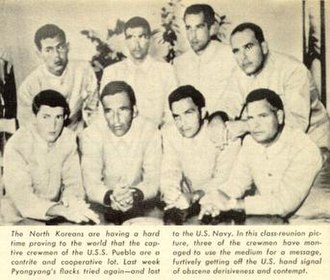 USS Pueblo (AGER-2) - North Korean Propaganda Photograph of prisoners of USS Pueblo. Photo and explanation from the Time article that blew the Hawaiian Good Luck Sign secret. The sailors were flipping the middle finger, as a way to covertly protest their captivity in North Korea, and the propaganda on their treatment and guilt. The North Koreans for months photographed them without knowing the real meaning of flipping the middle finger, while the sailors explained that the sign meant good luck in Hawaii.