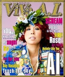 The album cover is produced in the format of a magazine cover. A mid-shot of Ai is featured against a pale pink background in the centre. She has a floral headdress, red hair and blue contacts, and is wearing a blue denim jacket with many button badges. Behind and above her head reads ViVa A.I. in a bordered font identitcal to US magazine Rolling Stone's font. To the left and right of Ai are the titles of the songs in blue, yellow and pink.