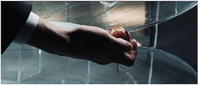 themes in minority report  the hand of a man wearing a tuxedo holds a wooden ball