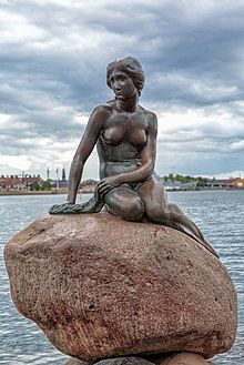 A statue of a mermaid sitting on a rock, surrounded by water.