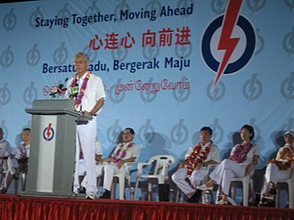 "Goh Chok Tong - Goh Chok Tong speaking at a rally at Potong Pasir during the 2006 general election. The banner behind him shows the campaign manifesto of the People's Action Party, ""Staying Together, Moving Ahead""."