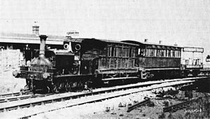 Steam locomotive with three different designs of carriage, at a railway station