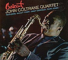 "A slanted photograph of Coltrane playing saxophone in a blue suit facing the left. The top left corner of the cover features the title of the album in red script with by the words ""John Coltrane Quartet"" in yellow beneath it and ""Featuring McCoy Tyner/Jimmy Garrison/Elvin Jones"" underneath that in blue."