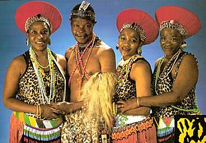 Mahotella Queens - Mahlathini and the Mahotella Queens, 1988. (L to r): Hilda Tloubatla, Mahlathini, Nobesuthu Mbadu, and Mildred Mangxola.