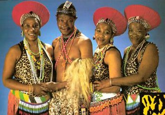 Mahlathini and the Mahotella Queens - Mahlathini and the Mahotella Queens, 1988. (L to r): Hilda Tloubatla, Mahlathini, Nobesuthu Mbadu, and Mildred Mangxola.