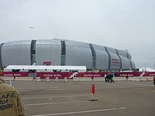 photo of State Farm Stadium taken from the parking lot, showing the domed stadium against an overcast sky