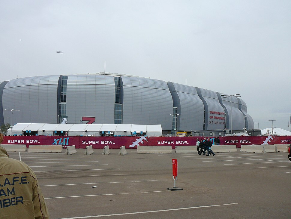photo of the University of Phoenix Stadium taken from the parking lot, showing the domed stadium against an overcast sky
