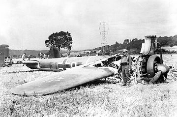A picture of a twin engine bomber aircraft lying in a field with its front end burnt out.