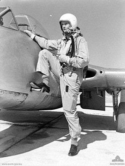 Man in flying suit and helmet climbing on to Vampire jet