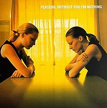 The album cover features two women sitting on a table in front of each other, looking down on the table. The light coming in from the curtains makes a yellow colour on the cover of the album.