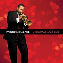 "Before a red background, a man in a suit is playing a trumpet with his eyes closed; the text ""Wynton Marsalis"