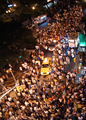 Crowd - A crowd of people returning from a show of fireworks spills into the street stopping traffic at the intersection of Fulton Street and Gold Street in Lower Manhattan