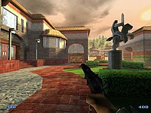A screenshot of an early development version of the game. The image shows the male player character holding a gun, in a courtyard, next to a building.