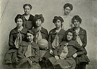 "Team photo of the 1903 KU women's basketball team with the middle girl holding a basketball with ""1903"" painted on it."