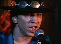 A young Caucasian man, who is wearing a wide, flat-brimmed black hat with a concho belt, sings into a microphone. Only his head and upper chest are shown.