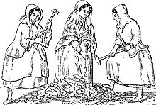Three women wearing heavy clothing and long bonnets, carrying long hammers, standing around a pile of rocks