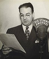 Black and white photograph of a male wearing glasses and standing next to a microphone