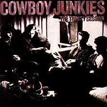 A grainy black-and-white photo of Cowboy Junkies sitting in a semicircle, with a rust-colored logo