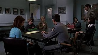 Final Destination 2 - A screenshot from the film showing the main cast of the film as their corresponding characters: (from left to right) A.J. Cook as Kimberly Corman, James Kirk as Tim Carpenter, Lynda Boyd as Nora Carpenter, Michael Landes as Officer Thomas Burke, Jonathan Cherry as Rory Peters, Terrence C. Carson as Eugene Dix, and Keegan Connor Tracy as Kat Jennings. Absent from the cast shot are Ali Larter as Clear Rivers and David Paetkau as Evan Lewis.
