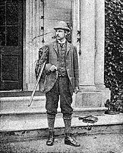 A young Rider Haggard standing at the steps of an English country house with a hunting gun uncocked in his arm