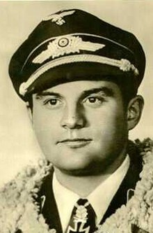 The head and shoulders of a young man, shown in semi-profile. He wears a peaked cap and a pilot's leather jacket with a fur collar, with an Iron Cross displayed at the front of his shirt collar.