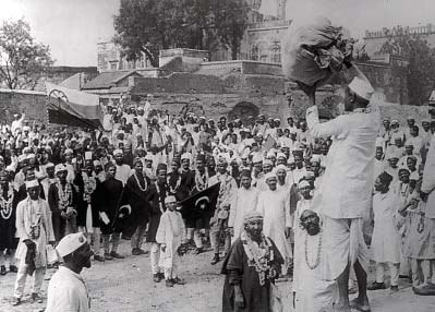 Hindus and Muslims, displaying the flags of both the Indian National Congress and the Muslim League, collecting clothes to be later burnt as a part of the non-co-operation movement initiated by Gandhi.