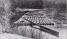 Black and white image of a raft made of long logs lashed together, tied to the bank of a stream. It has a large oar for steering.