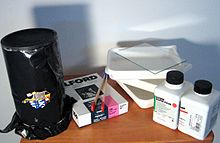 A pinhole camera made from an oatmeal container, wrapped in opaque plastic to prevent light leaks; a box of photographic paper; tongs and dishes for developing film; bottles of film developing chemicals