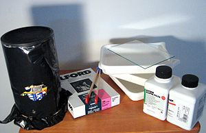 Pinhole camera - A home-made pinhole camera (on the left), wrapped in black plastic to prevent light leaks, and related developing supplies
