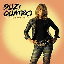 The front cover of Suzi Quatro's album In the Spotlight. Quatro is standing up with her hands on her hips. Behind her is yellow circle on an orange background, simulating the effect of a spotlight. She is wearing a black leather jacket (over a black top) and light blue jeans with horizontal holes ripped in them. She has two black leather belts - a plain one, plus one decorated with yellow studs and yellow chains.