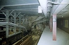 The Cortlandt Street station is seen partially collapsed. Several of the stations support beams are seen fallen. Debris covers the track. The front half of the station remains mostly intact.