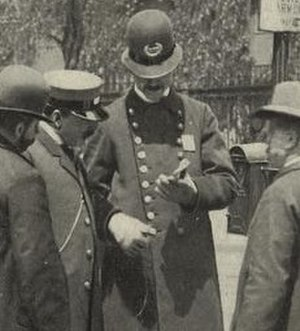 Police uniforms of the United States - A New York City police officer, wearing a custodian helmet, answers a visitor's questions at the corner of Fulton and Broadway in 1899.