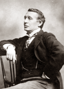 White middle-aged man, clean-shaven, in morning coat, seated in left semi-profile