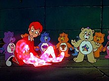 A boy dressed in red looks down at a girl with a crystal glow. A yellow bear stands up with her hands outstretched; some of her partners are holding hands and chanting.
