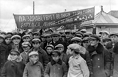 "Residents of a town in Eastern Poland (now West Belarus) assembled to greet the arrival of the Red Army during the Soviet invasion of Poland in 1939. The Russian text reads ""Long Live the great theory of Marx, Engels, Lenin-Stalin"" and contains a spelling error. Such welcomings were organized by the activists of the Communist Party of West Belarus affiliated with the Communist Party of Poland, delegalized in both countries by 1938. Belarus 1939 Greeting Soviets.jpg"