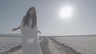 """Skyscraper (song) - Lovato as she is wandering through the desert in the music video for """"Skyscraper""""."""